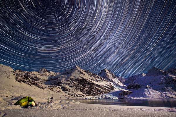 Star trails in the night sky above mountainous and snowy landscape
