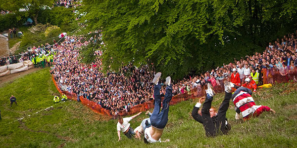 Several competitors tumble out of control down Cooper's Hill at Gloucestershire's cheese rolling contest