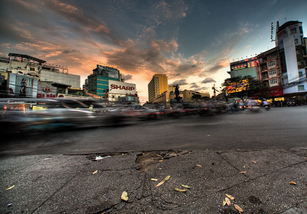 Motorcycles pack a road at sunset in Ho Chi Minh City