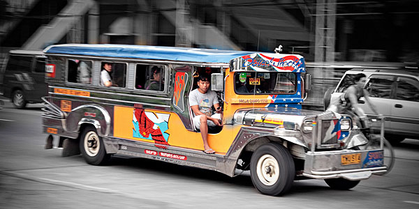A brightly coloured jeepney drives down a busy street