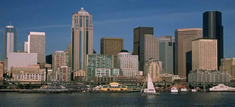 Sunshine illuminates the bustling Seattle Waterfront and the Seattle's skyline.
