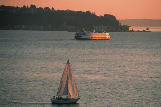 Pink light washes over a Washington state ferry and a small sail boat as the sun sets on Puget Sound