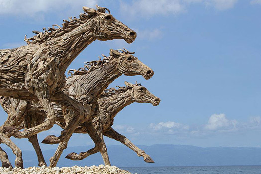 5 pictures of giant horses made of driftwood. On a beach. Some are running