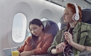 Young women friends with headphones and digital tablet on airplane