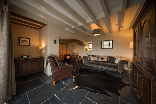 The parlour at Cappele Cottage in Snowdonia, with cosy throws for extra warmth during a Welsh winter.