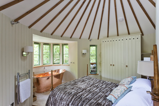 The Harptree Treehouse bedroom with king-size bed and copper bath.