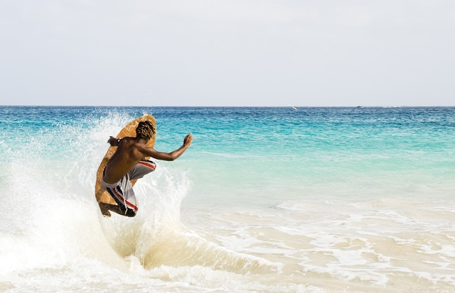 skimboarder jumping wave